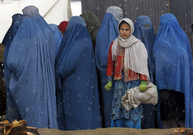 Afghan women wait to receive winter relief assistance donated by the Danish Refugee Council (DRC) in the outskirts of Kabul on February 3, 2013. © 2013 Reuters